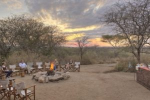 Olivers camp sundowners by the fire Tarangire